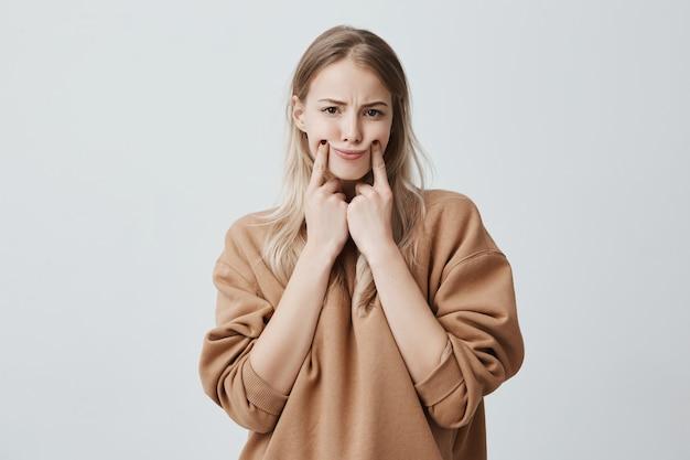 Schöne blonde frau macht grimasse, berührt ihre wangen mit den fingern, bringt sich zum lächeln, runzelt die stirn, ist unzufrieden und verärgert. gesichtsausdruck und negative emotionen