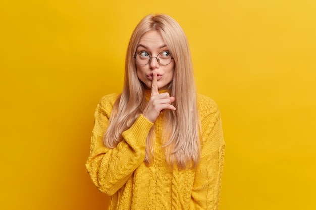 Schöne blonde frau macht stille geste versteckt geheimnis erzählt vertrauliche informationen hat mysteriösen ausdruck in freizeitkleidung gekleidet bittet, keinen lärm zu machen, macht shh zeichen. schweigen und geheimhaltung