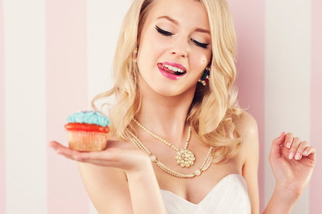 Schöne blonde frau mit blauem muffin