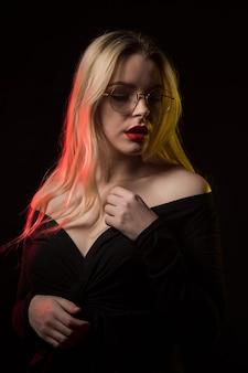 Schöne blonde frau mit brille trägt bluse mit nackten schultern, posiert mit rotem und gelbem licht