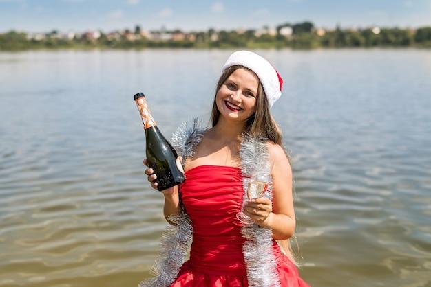 Schöne blonde frau mit champagner, der im wasser steht