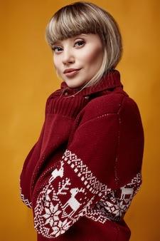 Schöne blonde frau mit dem kurzen haar in der weihnachtsstrickjacke