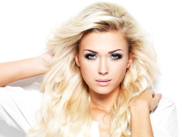 Schöne blonde frau mit dem langen lockigen haar - lokalisiert auf weiß