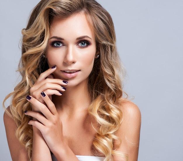 Schöne blonde frau mit dem langen lockigen haar