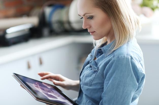 Schöne blonde frau mit digitaler tablette