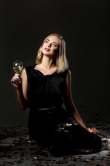 Schöne blonde frau mit einem glas weißwein auf einem schwarzen hintergrund