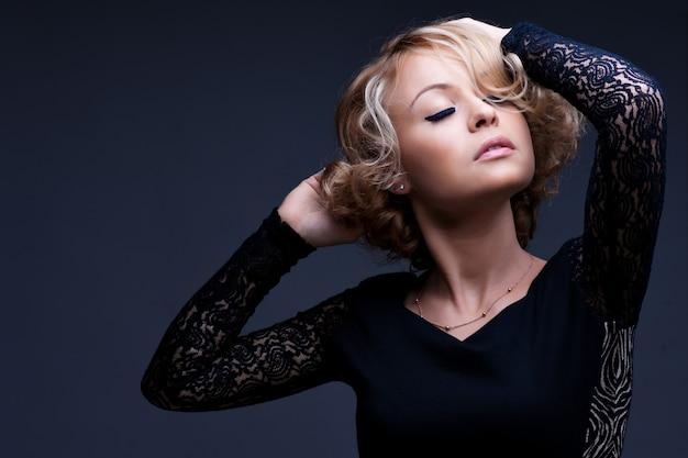 Schöne blonde frau mit elegantem schwarzem kleid.