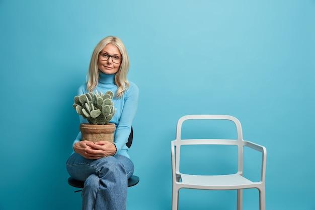 Schöne blonde frau mit europäischem aussehen hält topf kaktus sitzt allein in der nähe von leeren stuhl auf selbstisolation zu hause braucht live-kommunikation