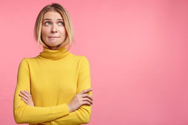 Schöne blonde frau mit gelbem rollkragenpullover