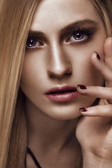 Schöne blonde frau mit gesunder haut und dem haar, rote maniküre, werfend im studio auf