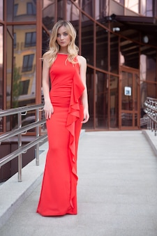 Schöne blonde frau mit großen blauen augen in einem roten kleid, das auf einer sommerstraße der stadt aufwirft