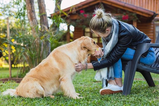 Schöne blonde frau mit ihrem labrador retriever. frau mit ihrem haustier in ihrem landhaus.