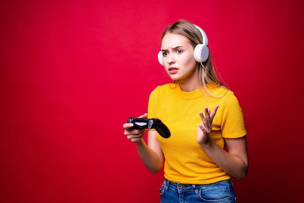 Schöne blonde frau mit joystick und kopfhörern an der roten wand