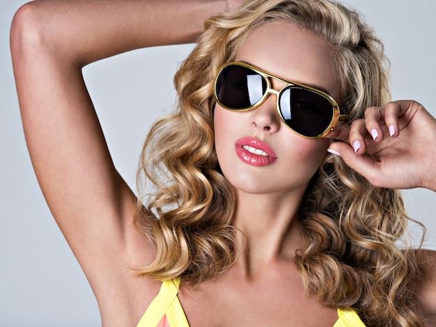 Schöne blonde frau mit langen gewellten haaren. attraktives junges mädchen trägt trendige sonnenbrille. sexy junges erwachsenes mädchen, das im studio - nahaufnahmeporträt aufwirft