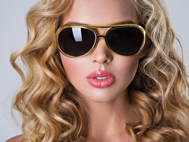 Schöne blonde frau mit langen gewellten haaren.