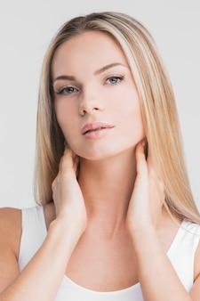 Schöne blonde frau mit langen glatten haaren auf einem weißen oberflächenschönheits-hautpflegekonzept