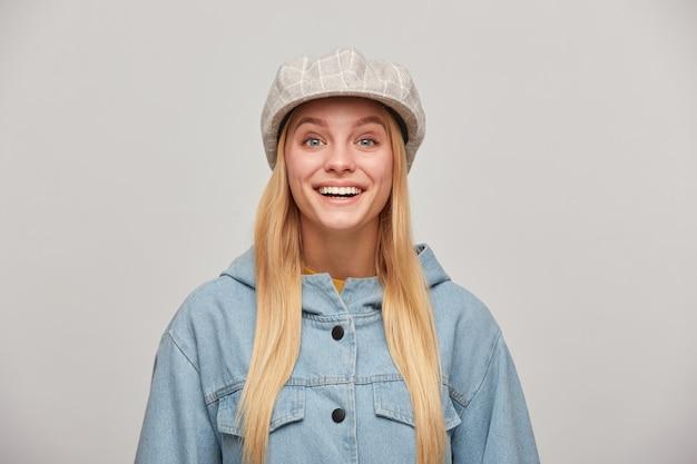 Schöne blonde frau mit langen haaren, kleinem lächeln, sieht froh aus, als würde man etwas angenehmes erwarten