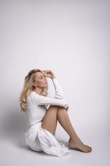 Schöne blonde frau mit langen haaren sitzt auf dem boden. dünnes mädchen mit langen beinen