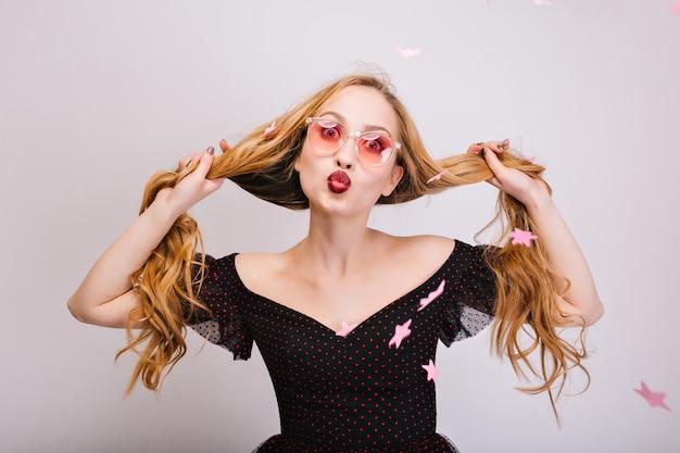 Schöne blonde frau mit langen lockigen haaren in den händen, die spaß haben, fröhliches mädchen, das kuss gibt, glücklich aussehend. trägt rosa brille, schwarzes hübsches kleid. rosa konfettisterne. isoliert..
