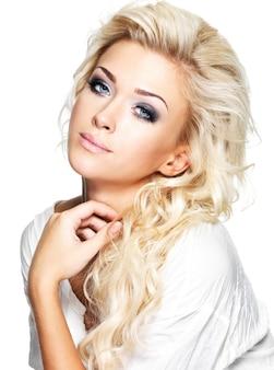 Schöne blonde frau mit langen lockigen haaren und stil make-up. mädchen, das auf weißem raum aufwirft