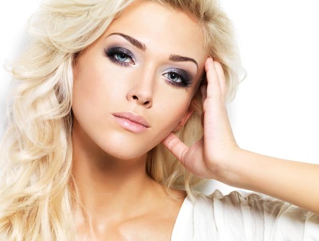 Schöne blonde frau mit langen lockigen haaren und stil make-up. mädchen, das auf weißer wand aufwirft