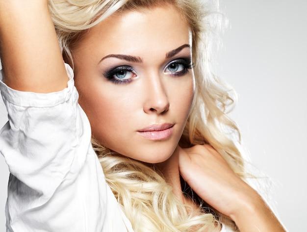 Schöne blonde frau mit langen lockigen haaren und stil make-up. mädchen, das im studio aufwirft