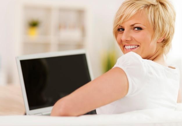 Schöne blonde frau mit laptop