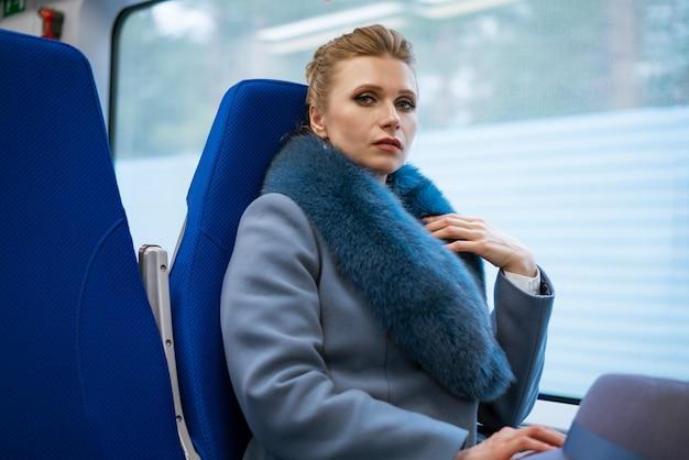 Schöne blonde frau mit make-up in einem blauen mantel reitet im zug posierend
