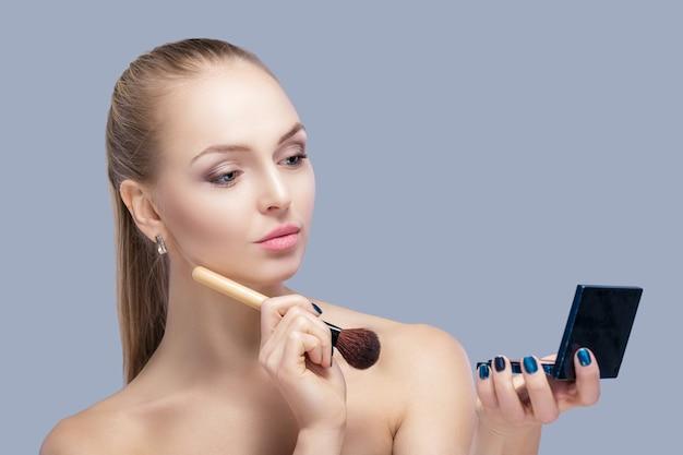Schöne blonde frau mit make-up-pinsel und blick in den spiegel auf grauem hintergrund. nahaufnahme