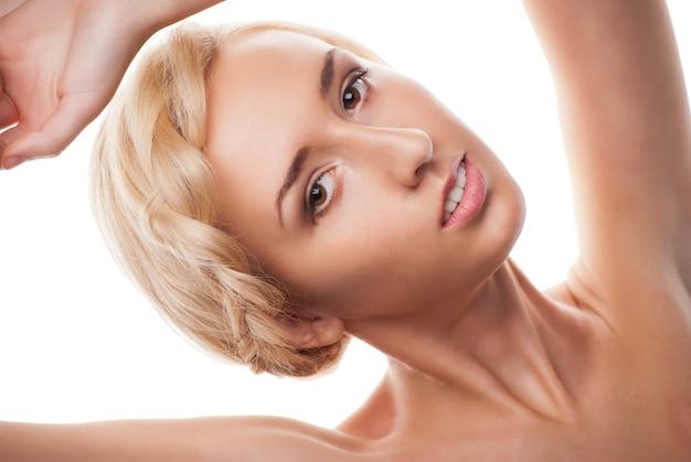 Schöne blonde frau mit modefrisur mit zopfelement - auf einem weißen