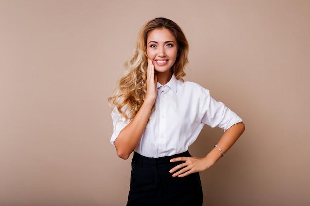 Schöne blonde frau mit perfektem lächeln in der weißen bluse, die über beige wand aufwirft. stilvolles workwear-outfit.