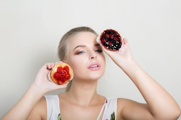 Schöne blonde frau mit professionellem make-up, die süße cupcakes mit beeren in der nähe ihres gesichts hält