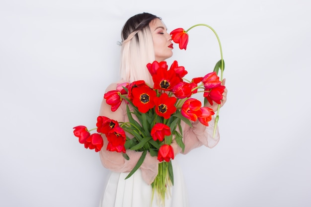 Schöne blonde frau mit roten tulpen