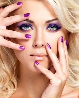 Schöne blonde frau mit schönheit lila maniküre und make-up der augen. model mit lockiger frisur.