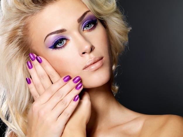 Schöne blonde frau mit schönheit lila maniküre und make-up der augen