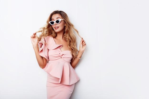 Schöne blonde frau mit überraschtem gesicht stehend. modisches, stilvolles kleid tragen. emotionales gesicht.