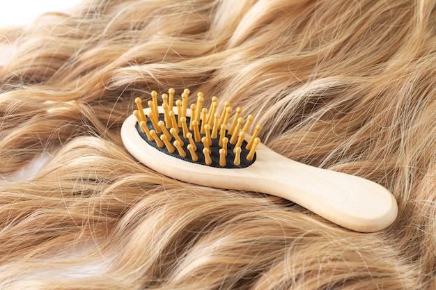 Schöne blonde frau mit welligem haar und bambuskammbürste