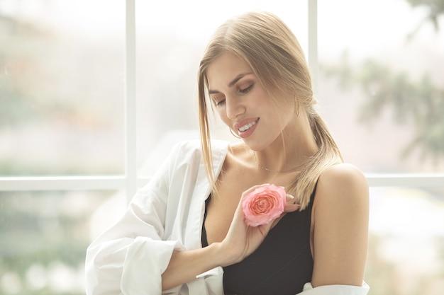 Schöne blonde frau mit zerbrechlicher rosenknospe perfektes hautschönheitskonzept