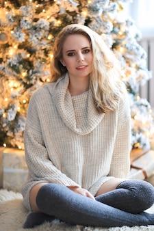 Schöne blonde frau neben dem weihnachtsbaum.