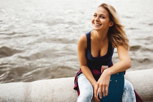 Schöne blonde frau posiert mit einem skateboard