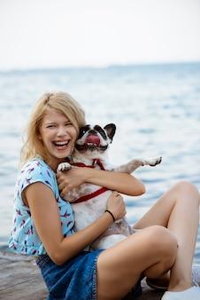 Schöne blonde frau sitzend, spielend mit französischer bulldogge nahe meer