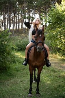 Schöne blonde frau steht mit einem pferd in der natur auf dem des waldes