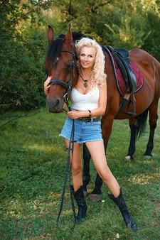 Schöne blonde frau steht mit einem pferd in der natur auf dem hintergrund des waldes