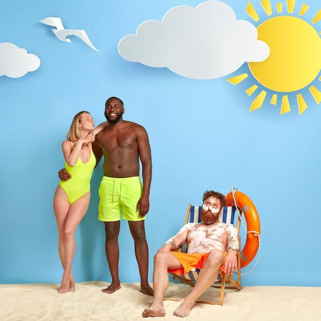 Schöne blonde frau steht mit freund nahe rotschopf, der am strand mit sonnencreme aufwirft