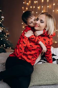 Schöne blonde frau umarmen ihr zartes sohnlied auf dem bett vor einem weihnachtsbaum