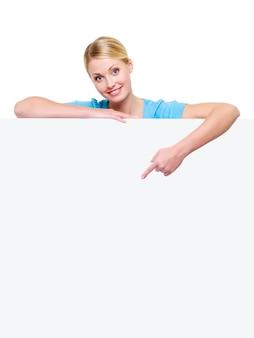 Schöne blonde frau unter dem leeren banner zeigt mit dem zeigefinger darauf