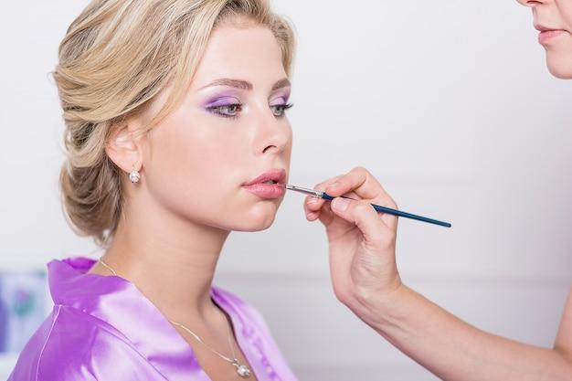 Schöne blonde frau wird von professionellen maskenbildner geschminkt