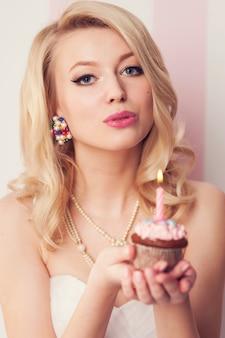 Schöne blonde frauenfeier mit muffin und kerze