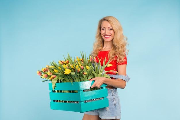 Schöne blonde gärtnerin, die box mit tulpen auf blauem hintergrund mit kopienraum hält