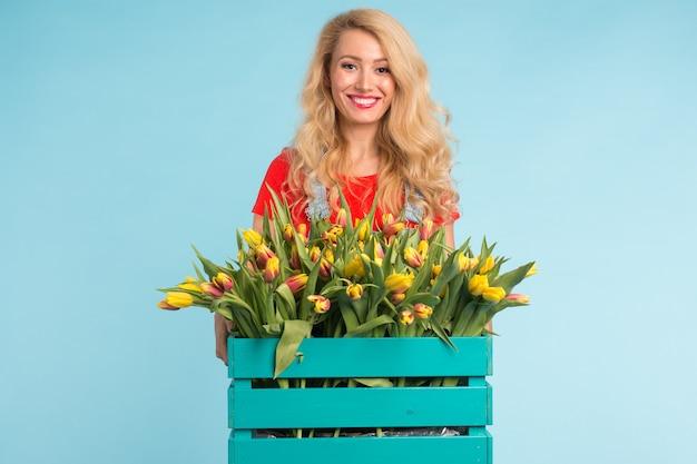 Schöne blonde gärtnerin, die box mit tulpen auf blauer oberfläche mit hält
